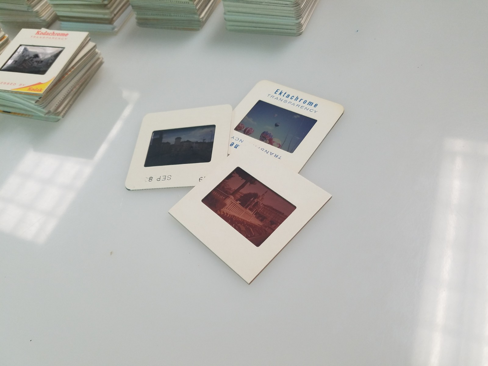 Three photography slides on a white table.